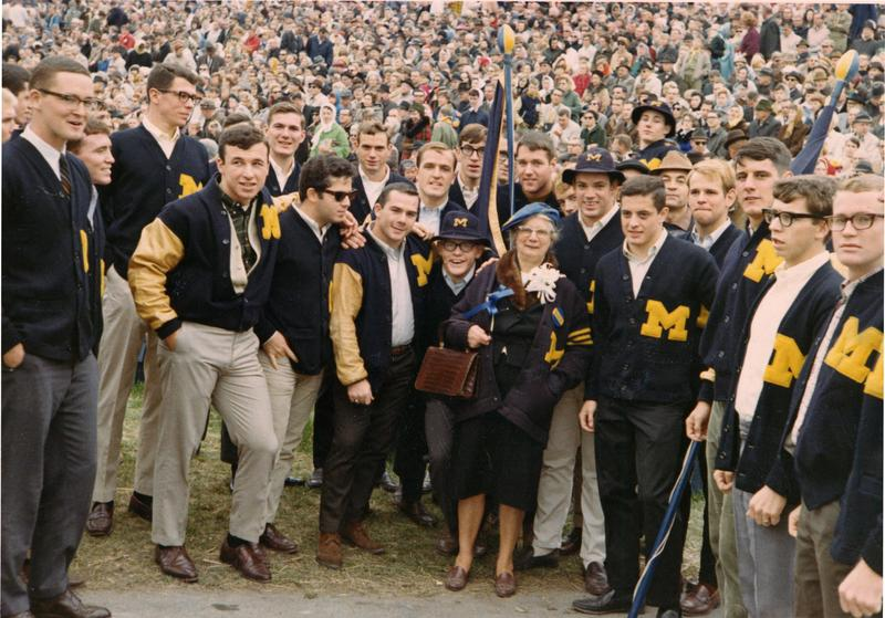 "Doc Hazel Losh with ""M"" men on field with two flags"