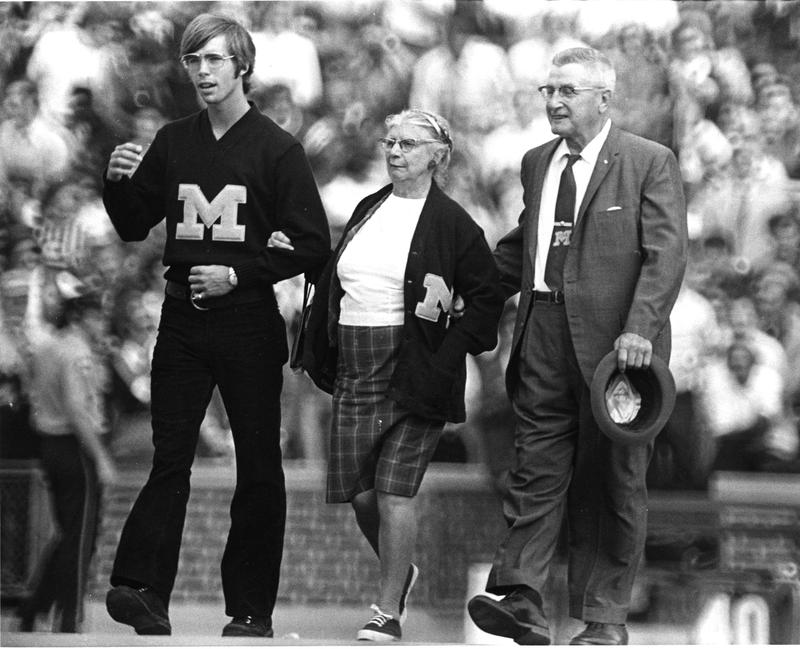 Doc Losh crossing the field with two men