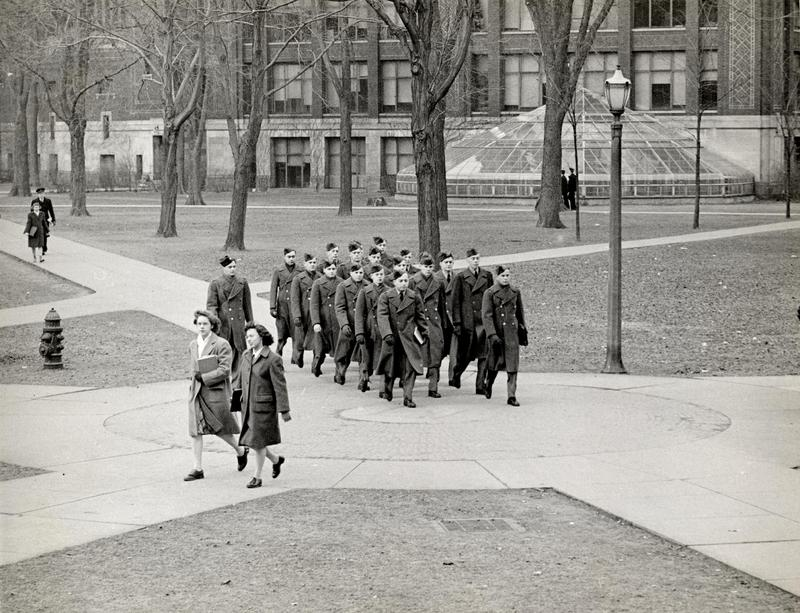 Two coeds cross path of military unit on Diag