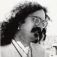 John Sinclair in wire rim glasses and small guitar earring