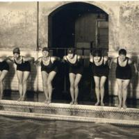 Women on edge of pool in swimsuits