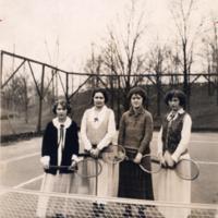 Four women pose on tennis court, circa 1918-1920.<br />